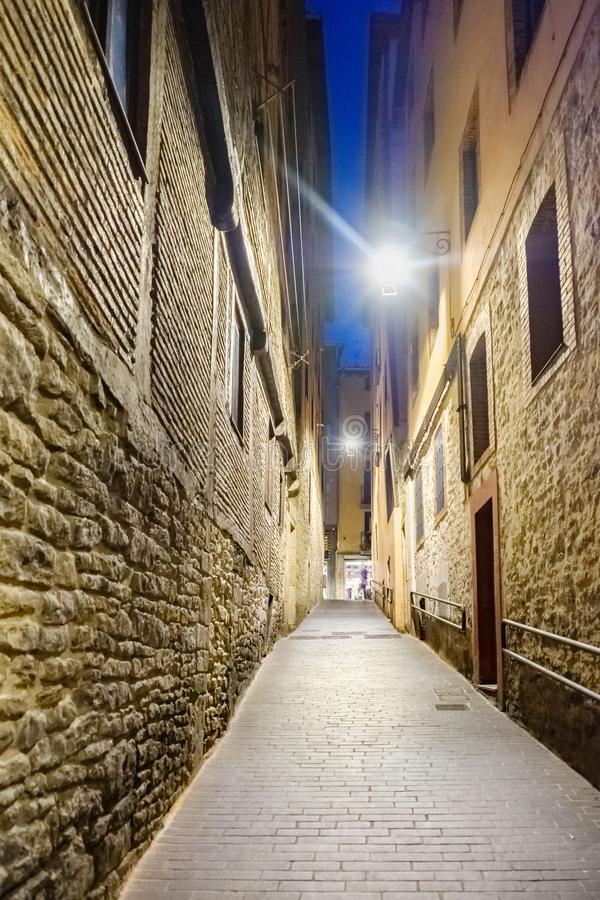 Night shot of a lonely and narrow cobblestone alley with facades of stone houses royalty free stock photography
