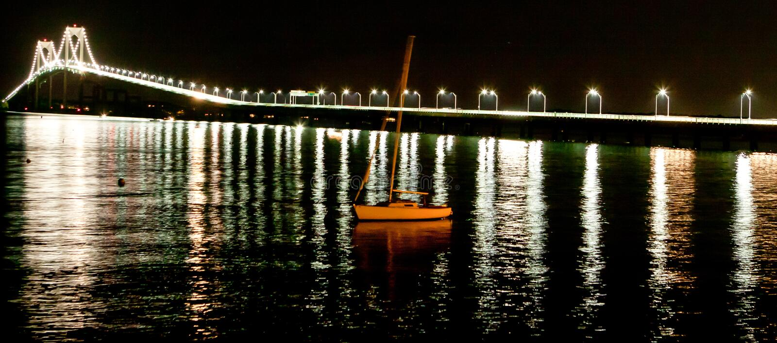 Night shot of Newport Bridge with sailboat stock photos