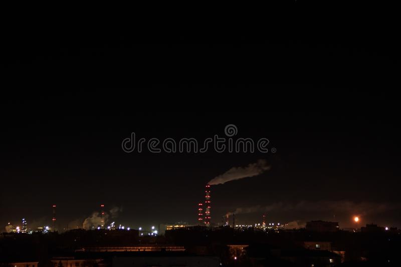 Night shot of the oil refinery on the city skyline. Lots of lights. Industrial and residential areal. Air Pollution stock photo