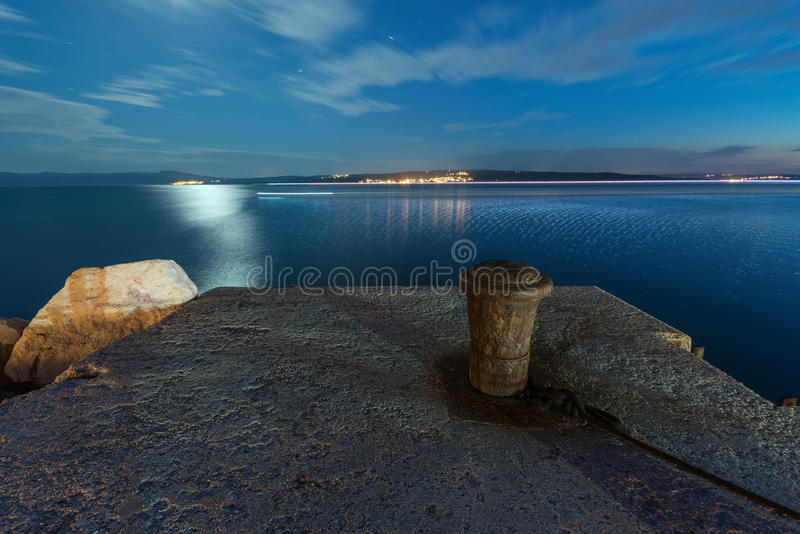 Night shot of old bollard on the pier with distant island town stock images