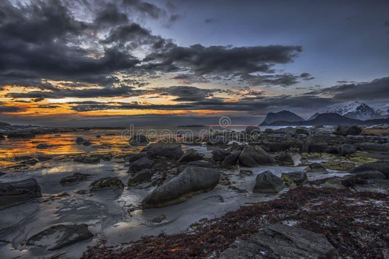 A coastal view from Flakstad island, lofoten islands. A night shot photo from Sandnes in Flakstad, Lofoten, showing a decending sun making beautiful reflections stock photos
