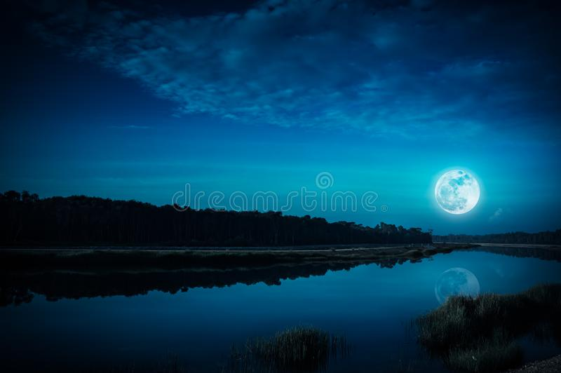 Night sky and bright full moon at riverside. Serenity nature background. Beautiful landscape of blue sky with cloud and full moon above silhouettes of trees at royalty free stock photos