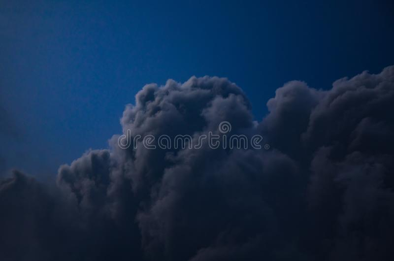 Night sky with cumulus cloud. Background of a dark blue sky, a night sky with a cumulus, a moonlight feeding to a cloud stock photo