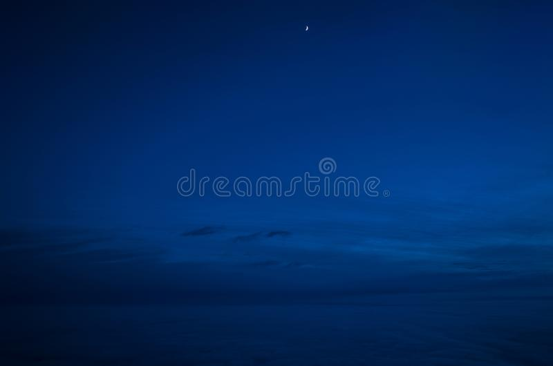 Night sky of dark blue color and strong clouds and very small moon silhouette stock image