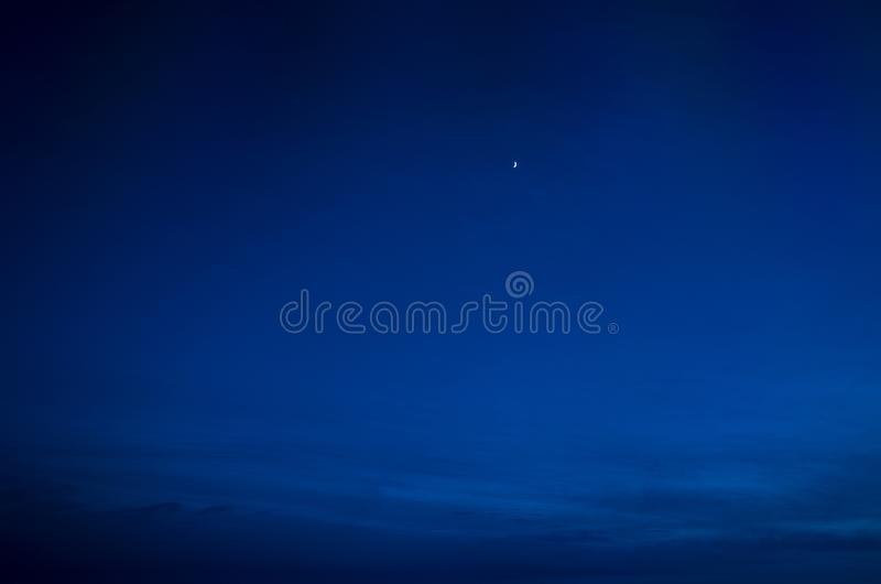 Night sky of dark blue color and strong clouds and very small moon silhouette.  stock photography