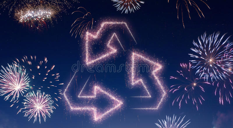 Night sky with fireworks shaped as recycling arrows.series. A dark night sky with a sparkling red firecracker in the shape of recycling arrows composed into royalty free illustration