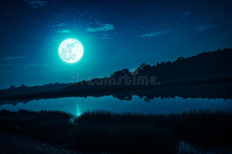 Night sky with full moon and many stars, serenity nature backgro. Beautiful landscape of blue sky with many stars and full moon above silhouettes of trees at stock photography