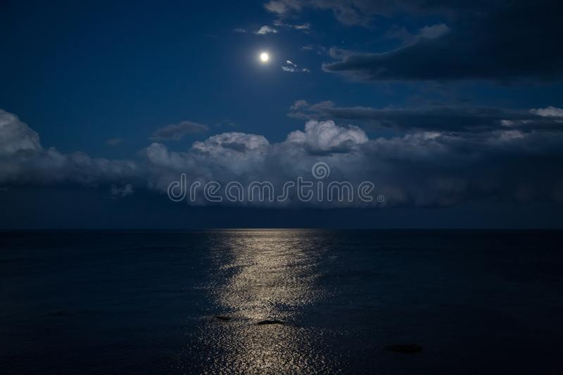 Night sky with full moon and reflection in sea, beautiful clouds. royalty free stock photo