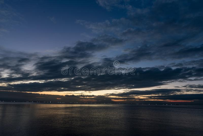 Night Sky in Manila, Philippines. Ocean Water and Cloudy Sky royalty free stock photo