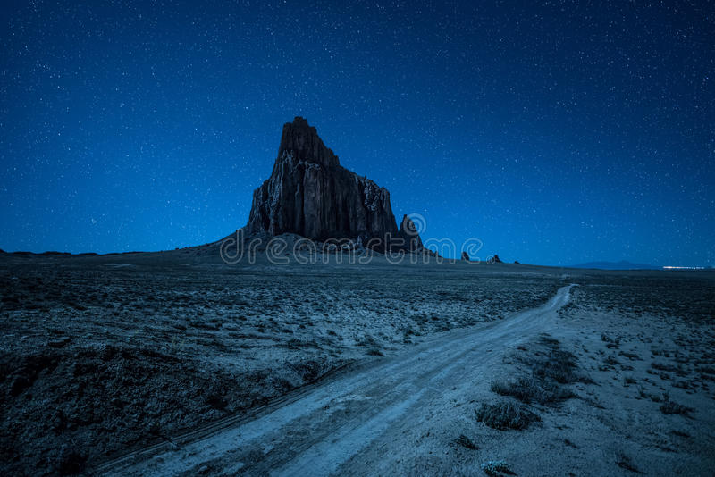 Night sky with many stars above Shiprock in New Mexico. Night sky with many stars above Shiprock and a dirt road. Shiprock is a great volcanic rock mountain stock image