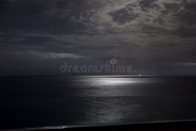 Night sky with moonlight clouds. And sea stock image