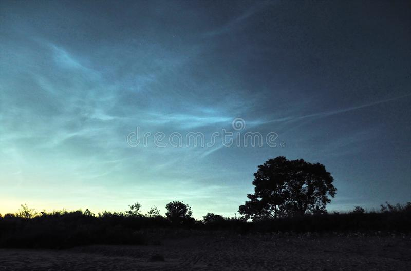Night sky and Noctilucent clouds over sea stock photography