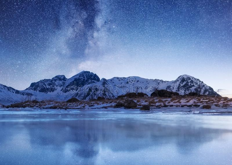 Night sky and reflection on the frozen lake. Natural landscape in the Lofoten islands, Norway. stock image