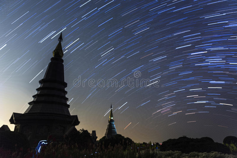 Night sky with star trail and two pagoda in Doi Inthanon mountain, natural astronomy landscape stock photography
