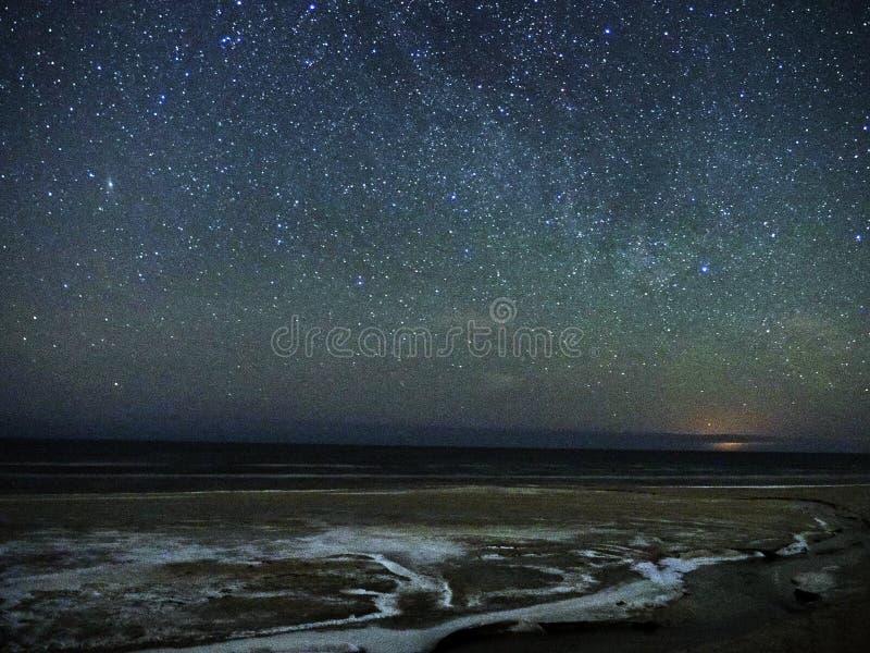 Night sky stars and snow on sea coast stock photography