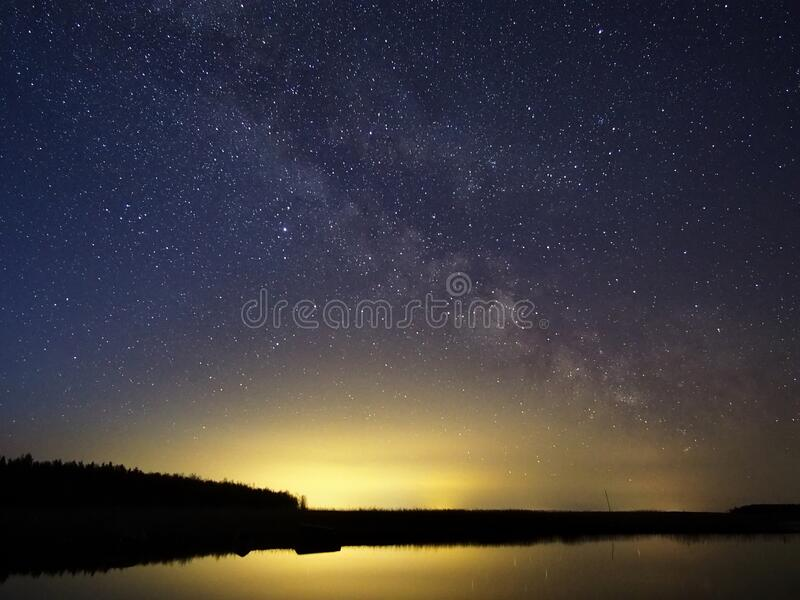 Night sky stars and  milky way over lake stock photo