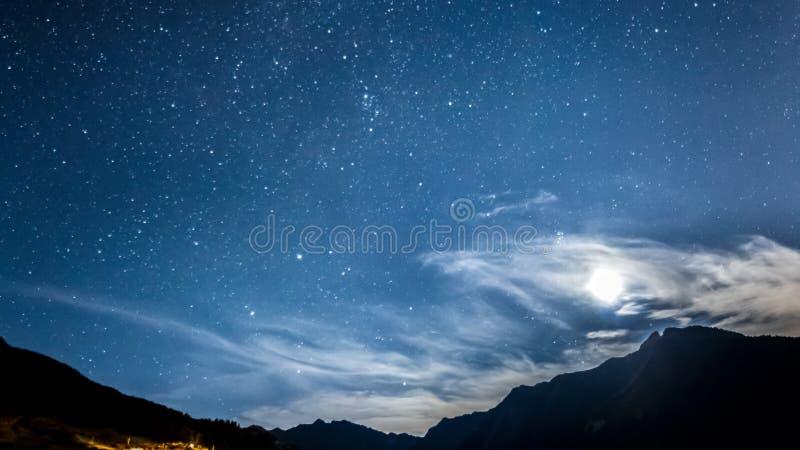 Night sky stars and moon across mountain stock photo