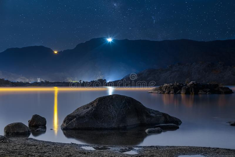 Night sky stars over mountain lake. Summer starry night royalty free stock images