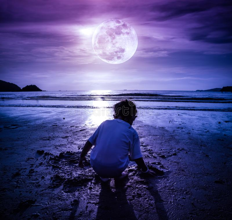 Night sky with super moon. Girl digging in sand. Concept of connecting children with nature. Landscape of night sky with super moon. Back view of young girl stock image