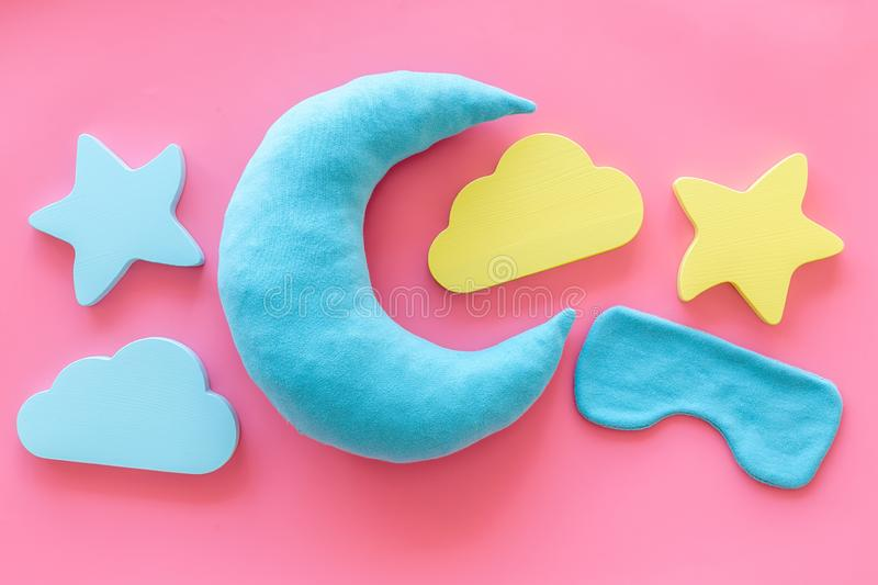 Night sleep concept with moon, clouds, stars toys and blindfold on pink background top view. Good dreams. Night sleep concept with moon, clouds, stars toys and stock photo