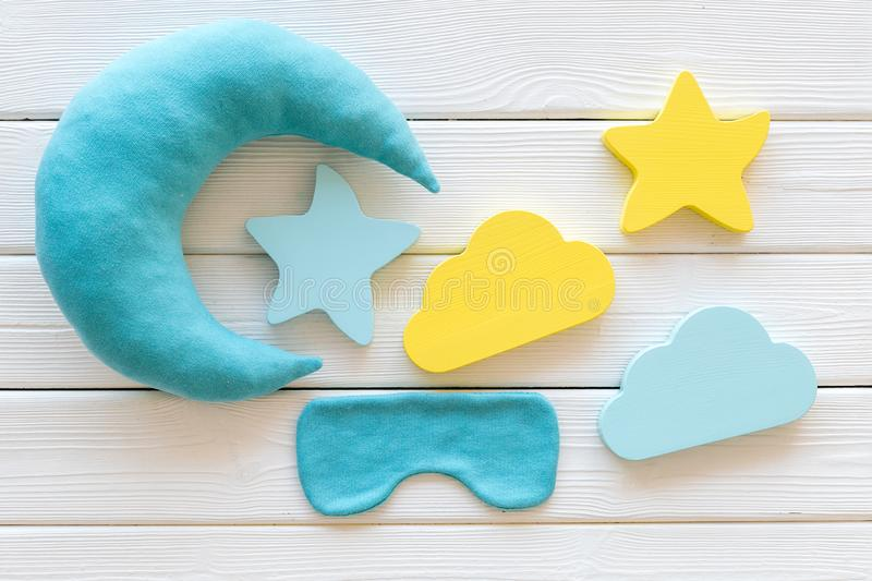 Night sleep concept with moon, clouds, stars toys and blindfold on white wooden background top view. Good dreams. Night sleep concept with moon, clouds, stars stock image