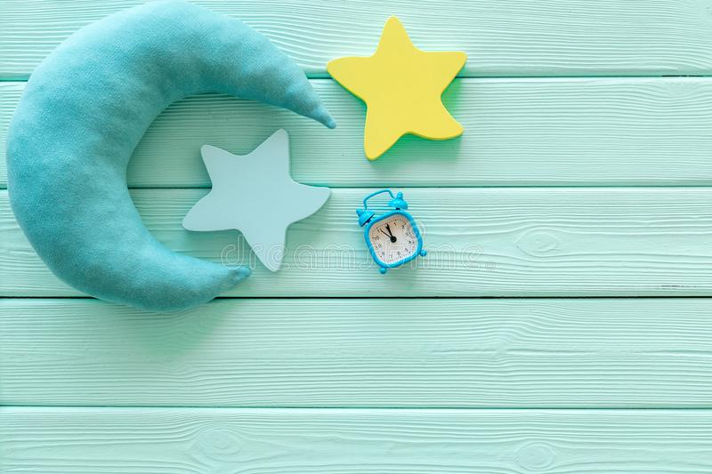 Night sleep concept with moon and clouds toys and alarm clock on mint green wooden background top view mockup. Good dreams. Night sleep concept with moon and stock photo