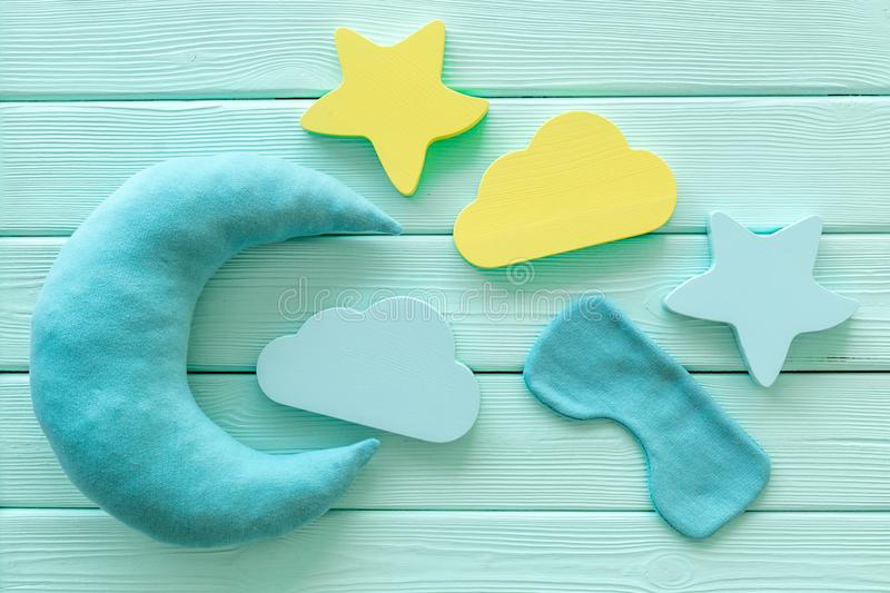 Night sleep concept with moon, stars, clouds toy and mask on mint green wooden background top view. Good dream. Night sleep concept with moon, stars, clouds toy royalty free stock photos