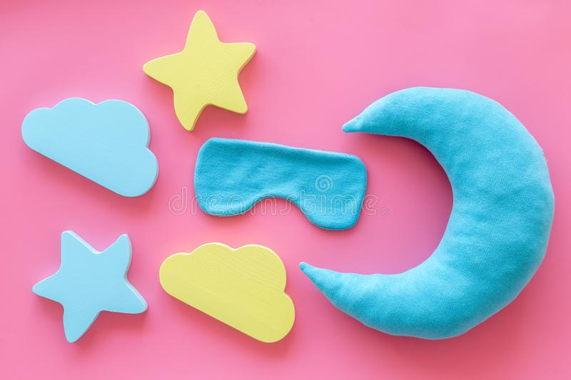 Night sleep concept with moon, stars, clouds toy and mask on pink background top view. Good dream. Night sleep concept with moon, stars, clouds toy and mask on stock images