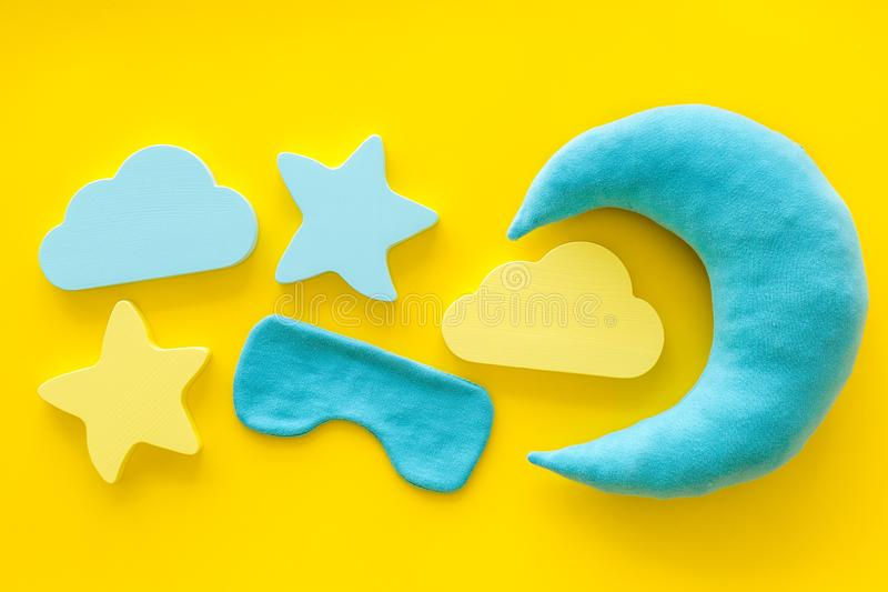Night sleep concept with moon, stars, clouds toy and mask on yellow background top view. Good dream. Night sleep concept with moon, stars, clouds toy and mask on royalty free stock photography