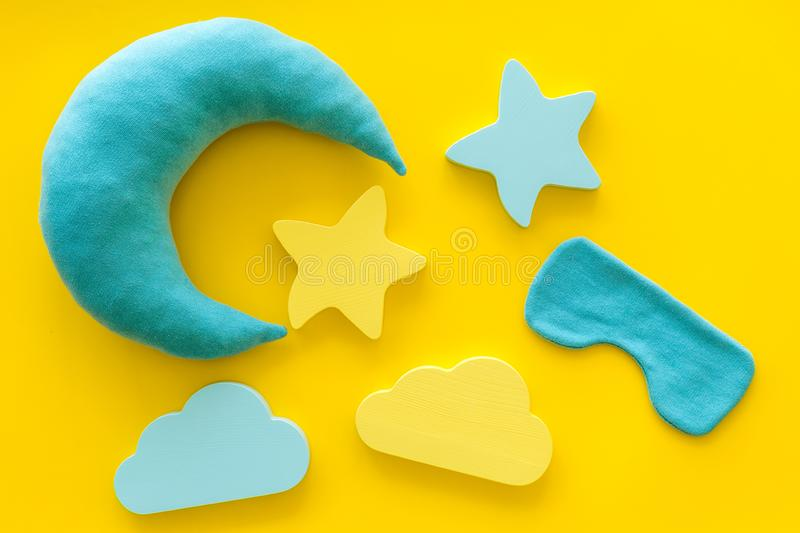 Night sleep concept with moon, stars, clouds toy and mask on yellow background top view. Good dream. Night sleep concept with moon, stars, clouds toy and mask on royalty free stock photo