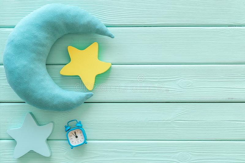 Night sleep concept with moon, stars toy and alarm clock on mint green wooden background top view copy space. Good dream. Night sleep concept with moon, stars royalty free stock photo