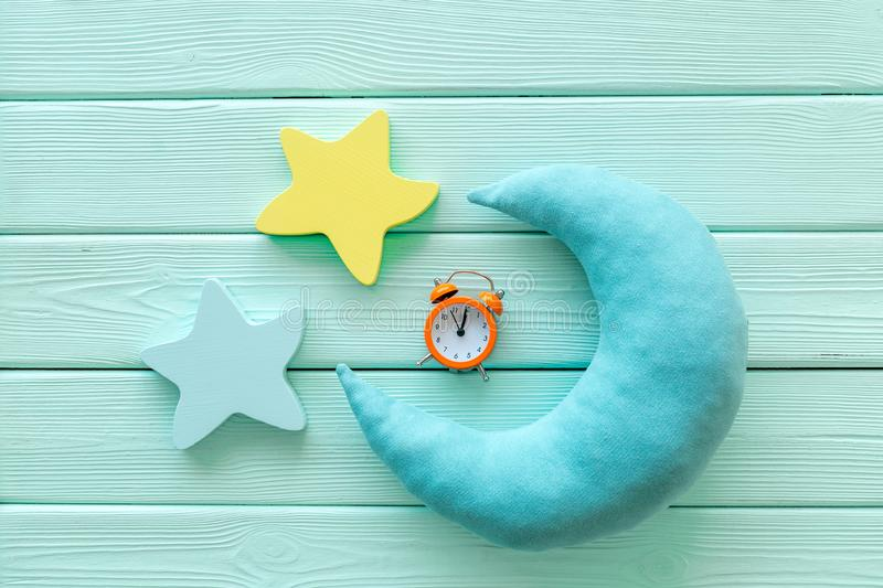 Night sleep concept with moon, stars toy and alarm clock on mint green wooden background top view. Good dream. Night sleep concept with moon, stars toy and alarm stock photography