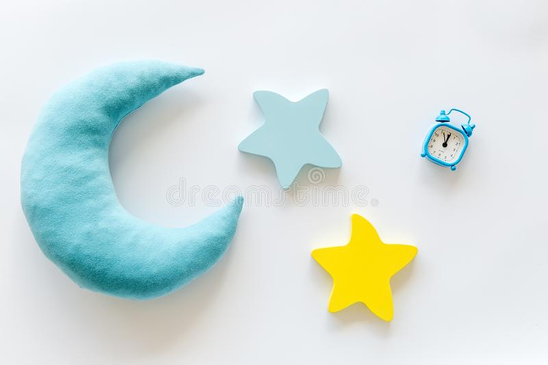 Night sleep concept with moon, stars toy and alarm clock on white background top view. Good dream. Night sleep concept with moon, stars toy and alarm clock on royalty free stock photography