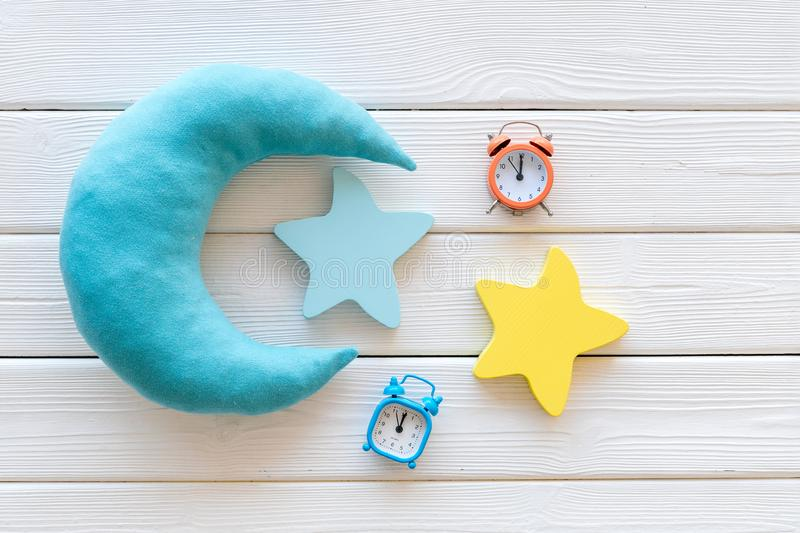 Night sleep concept with moon, stars toy and alarm clock on white wooden background top view. Good dream. Night sleep concept with moon, stars toy and alarm royalty free stock photography