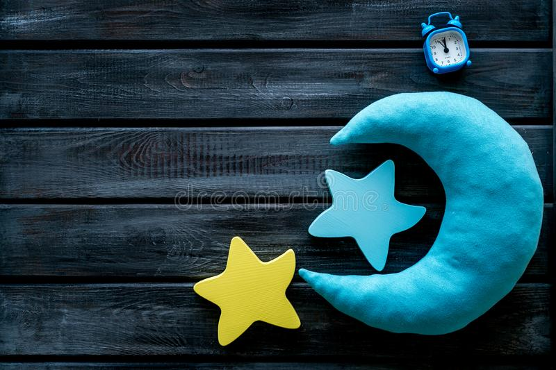 Night sleep concept with moon, stars toy and alarm clock on wooden background top view copy space. Good dream. Night sleep concept with moon, stars toy and alarm royalty free stock photography