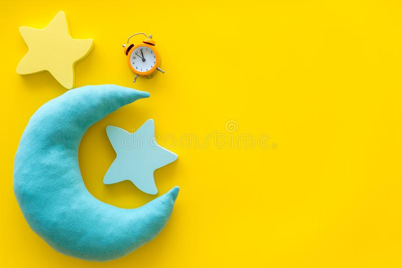 Night sleep concept with moon, stars toy and alarm clock on yellow background top view copy space. Good dream. Night sleep concept with moon, stars toy and alarm royalty free stock image