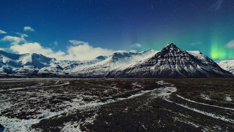 Night, Snow, Natural Phenomenon, Winter, Aurora Borealis. Beautiful landscape with high mountains with illuminated stock image