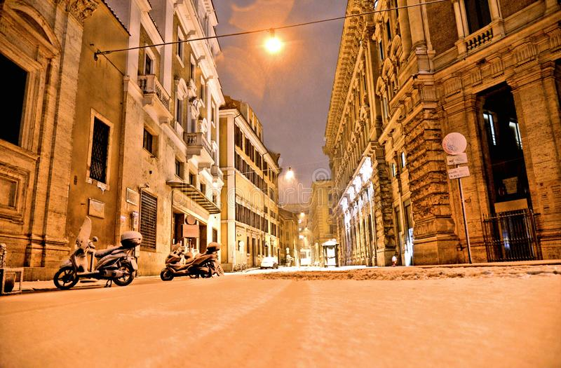 Night snowfall in empty street in the historic center of Rome with cars and road surface completely covered by snow stock photo