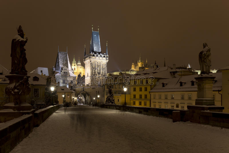 Night snowy colorful Prague Lesser Town with gothic Castle, St. Nicholas` Cathedral from Charles Bridge, Czech republic. Night snowy Prague Lesser Town with royalty free stock photos