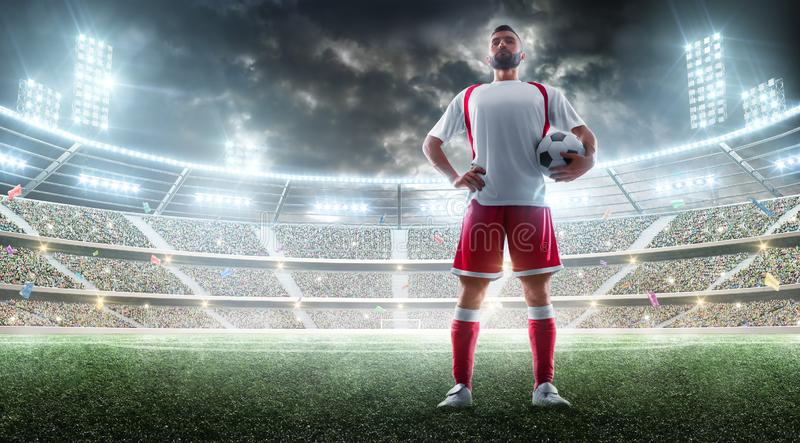 Night stadium panorama. Soccer player holds a soccer ball. Sport concept. Mockup royalty free stock photos