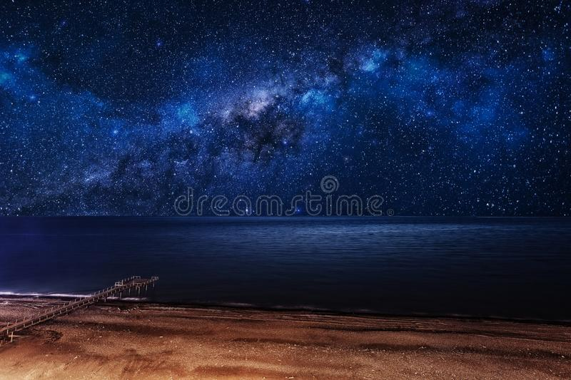 Milky Way over the sea. Night starry sky over the beach with a pier royalty free stock photo