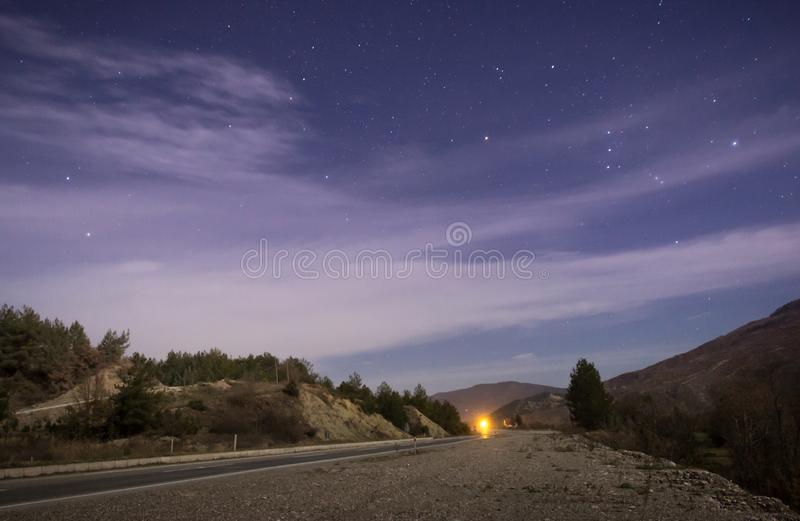 A night with stars and road. Long exposure photo of purple sky night with stars and clouds, road and yellow light royalty free stock photo