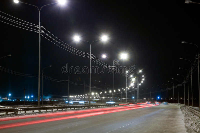 Night street. With traces from light of headlights shined with street lanterns royalty free stock photography