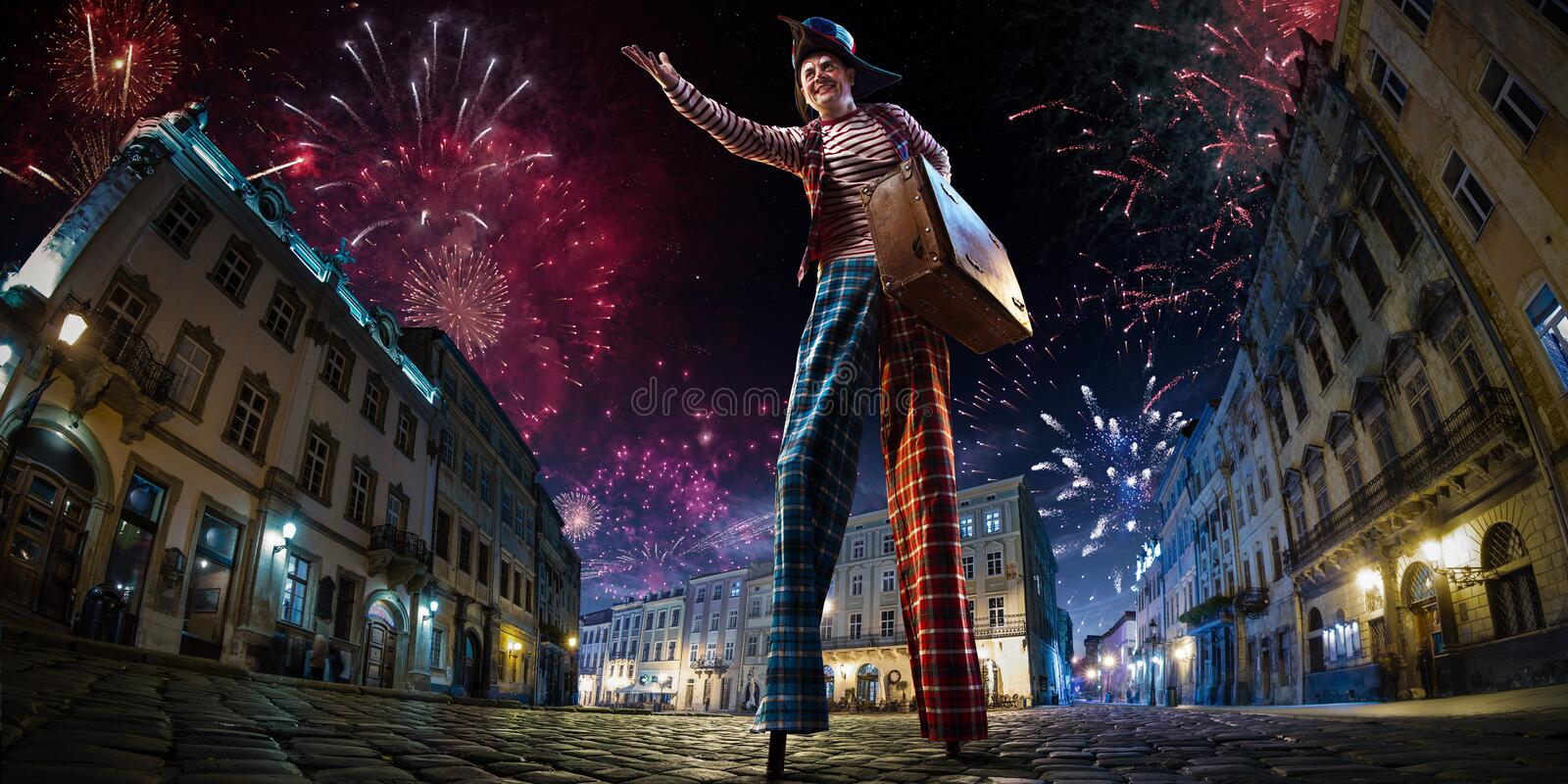 Night street circus performance whit clown. Festival city background. fireworks and Celebration atmosphere. Wide engle photo stock photos
