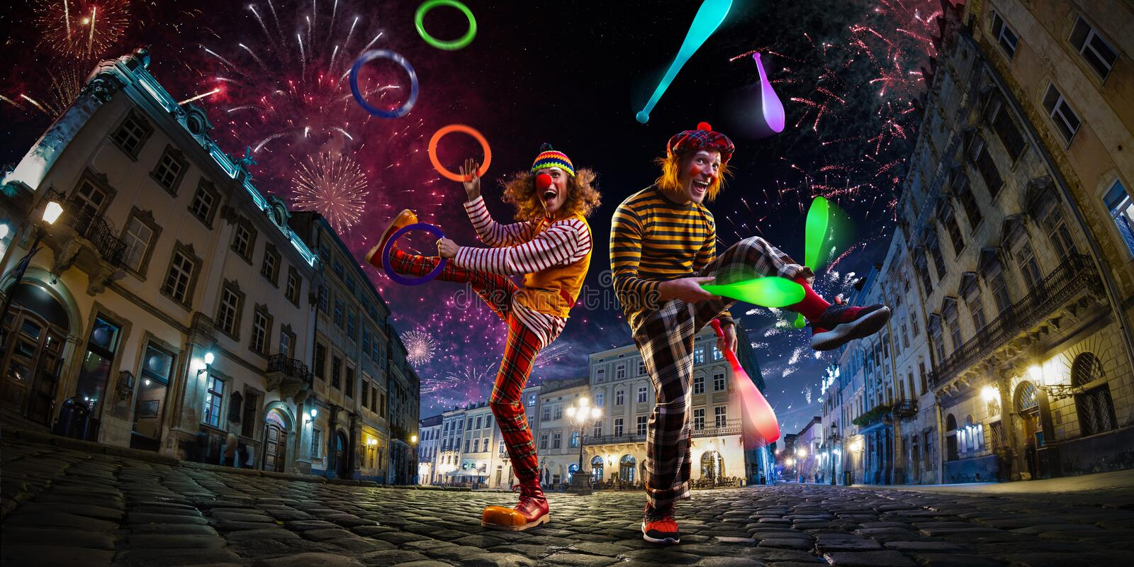 Night street circus performance whit two clowns, jugglerFestival city background. fireworks and Celebration atmosphere.Wide engle stock photography