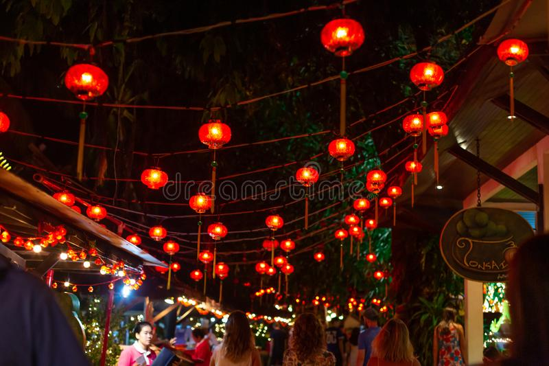 Night street decorated with red Chinese lanterns over people`s heads.  stock photos