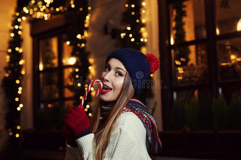 Night street portrait of a smiling beautiful young woman biting candy cane. Lady wearing classic winter knitted clothes royalty free stock photo