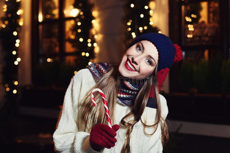 Night street portrait of smiling beautiful young woman with Christmas candy cane. Model looking at camera. Lady wearing royalty free stock photos