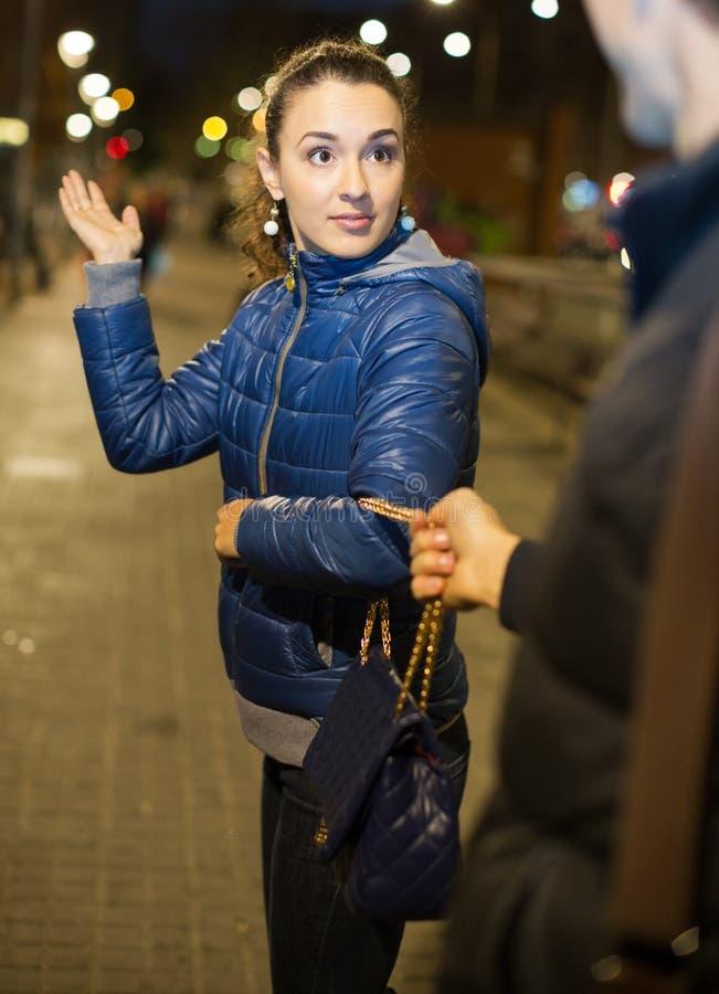 Night street robbery scene. Men taking away female bag royalty free stock image