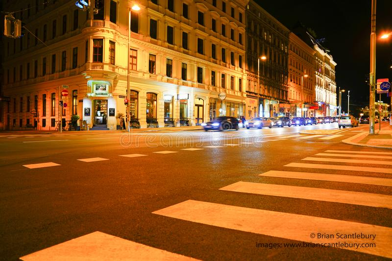 Night street scene from street level view people, cars, pedestrian crossing in night lights from street and surrounding shops and stock images